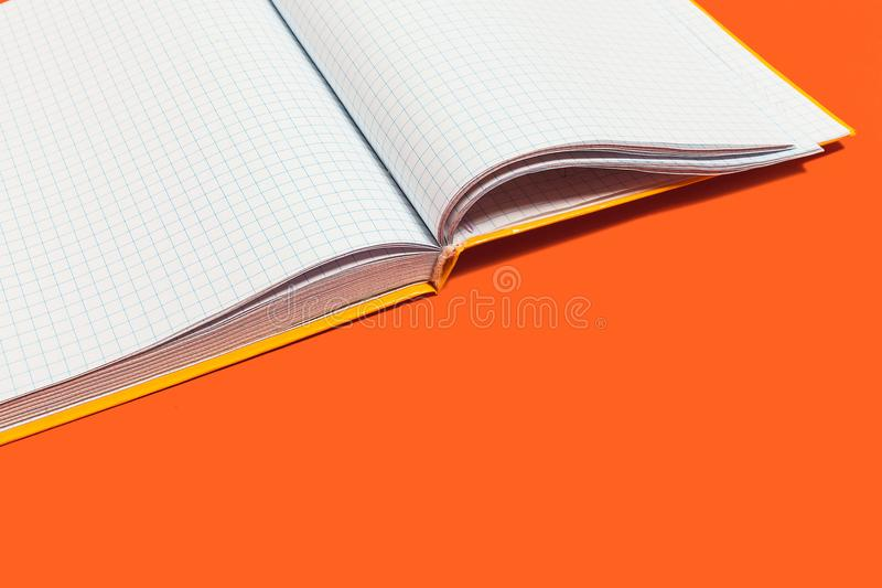 Opened workbook on an orange surface. White opened workbook lying on an orange background. concept of business or educational equipment. free space for royalty free stock photography