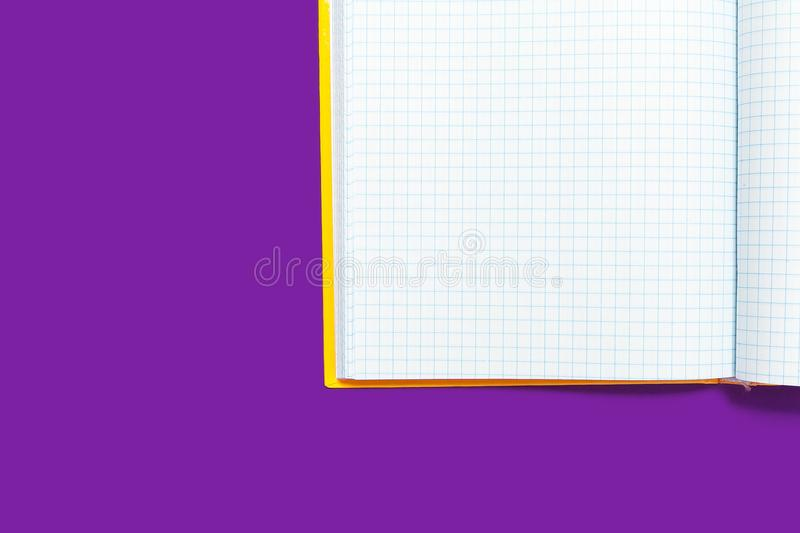 Opened workbook on a purple background. White opened workbook lying on a purple background. concept of business or educational equipment stock photography