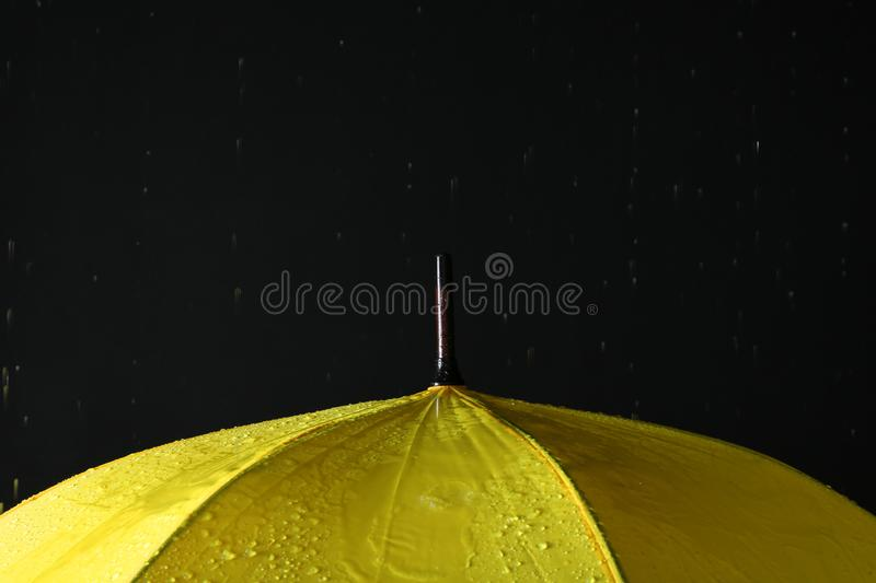 Opened yellow umbrella under rain against black background stock photography