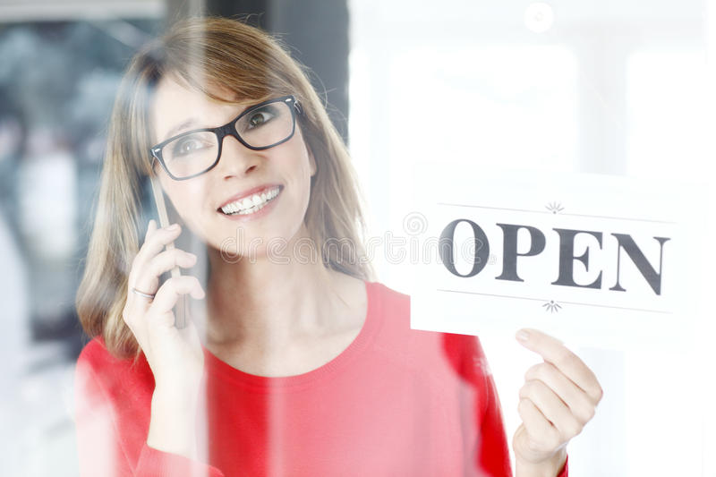 Opening all day. Portrait of middle aged woman holding an open sign and making call at her small shop royalty free stock photography