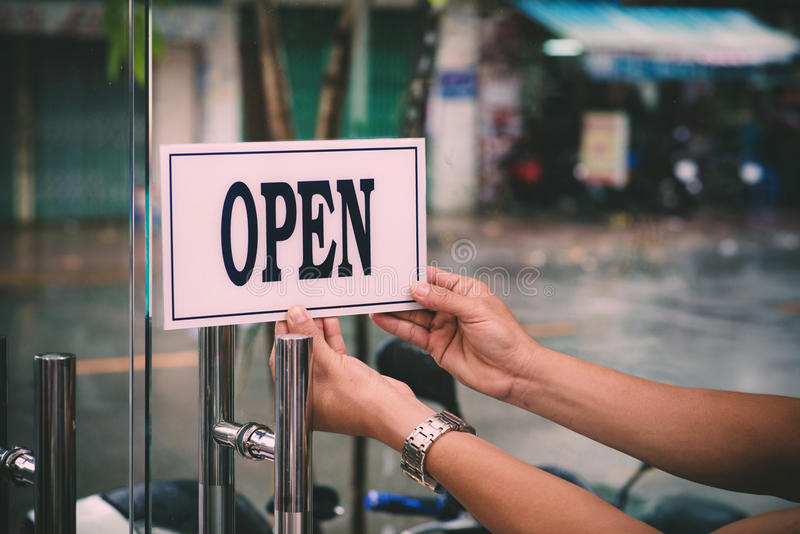 Opening barbershop. Hands of hairdresser turning card to open barbershop royalty free stock image