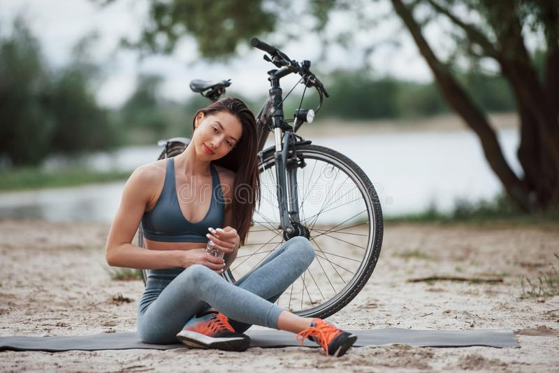 Opening bottle with water. Female cyclist with good body shape sitting near her bike on beach at daytime.  stock image