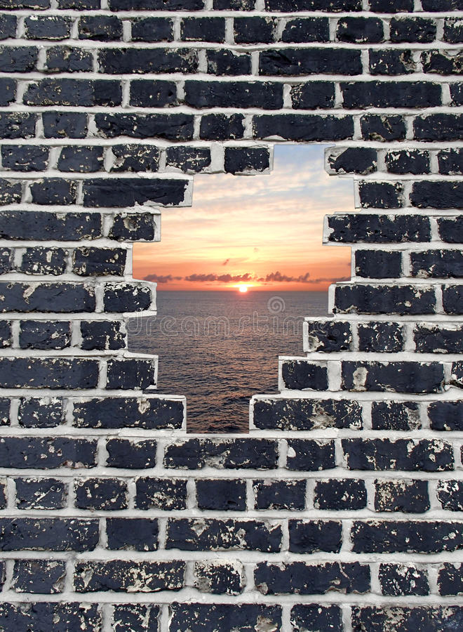 Opening in a brick wall, sunset on sea royalty free stock photos