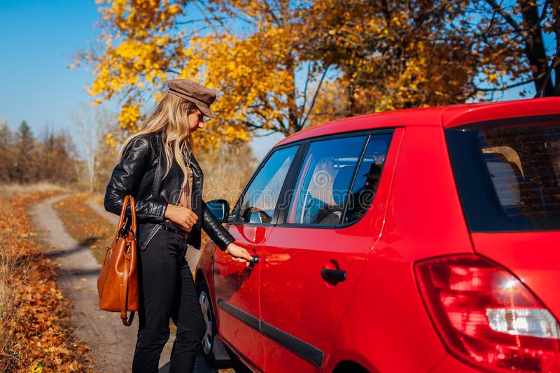 Opening car door. Woman opens red car with key on autumn road stock photos
