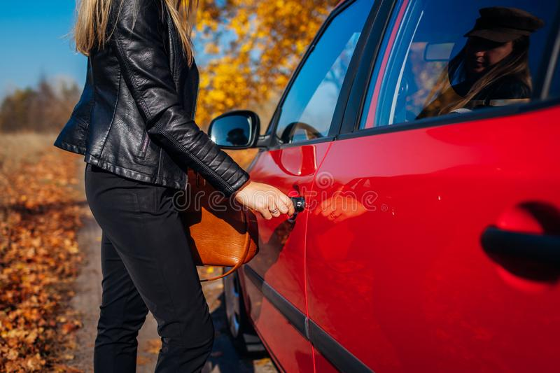 Opening car door. Woman opens red car with key on autumn road. Driver ready to go royalty free stock photo