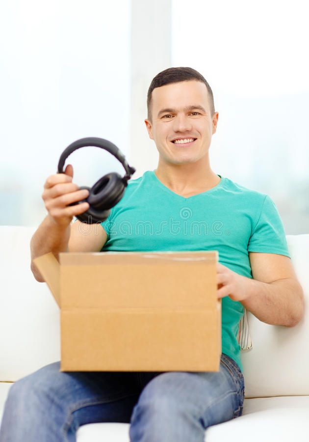 Opening cardboard box and taking out headphones. Post, home, technology and lifestyle concept - smiling man opening cardboard box with headphones in it stock images