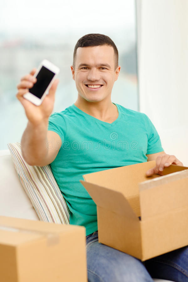Opening cardboard box and taking out smartphone. Post, home, technology and lifestyle concept - smiling man opening cardboard box with smartphone in it stock image
