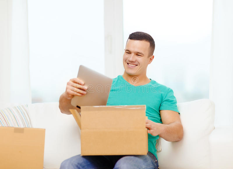 Opening cardboard box and taking out tablet pc. Post, home, technology and lifestyle concept - smiling man opening cardboard box with tablet pc computer in it royalty free stock photography