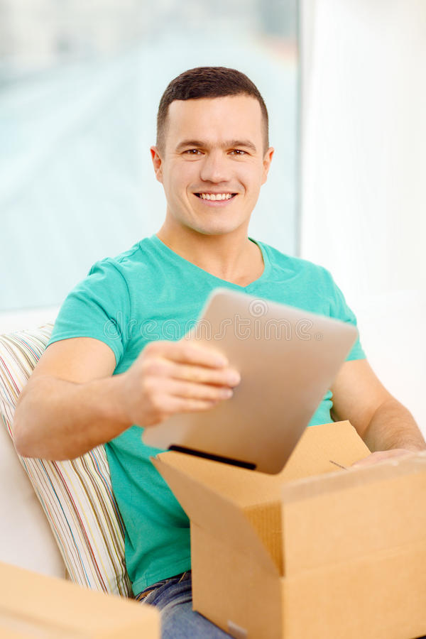 Opening cardboard box and taking out tablet pc. Post, home, technology and lifestyle concept - smiling man opening cardboard box with tablet pc computer in it royalty free stock image