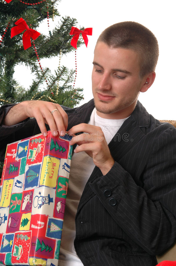 Opening Christmas Gift. A handsome young man opening a Christmas gift by the tree stock photography