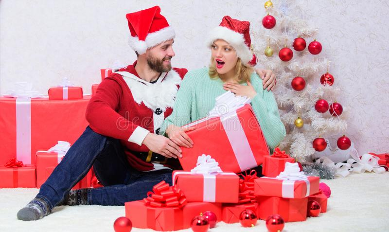 Opening christmas present. Loving couple unpacking gift christmas tree background. What a surprise. Couple in love happy stock photo