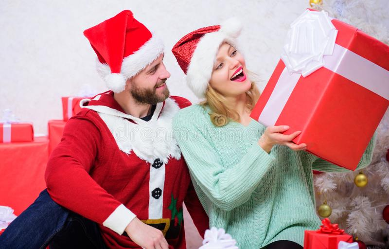 Opening christmas present. What a surprise. Loving couple unpacking gift christmas tree background. Husband prepared stock image