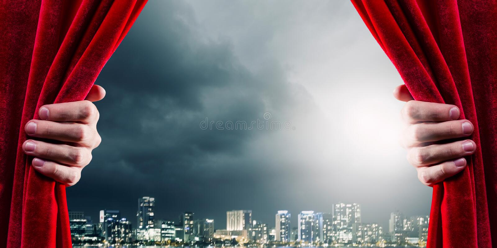 Opening curtain. Close up of hand opening red curtain. Place for text royalty free stock image