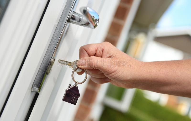 Opening a door to house with key. Opening a front door to house with key concept of security or new home stock photography