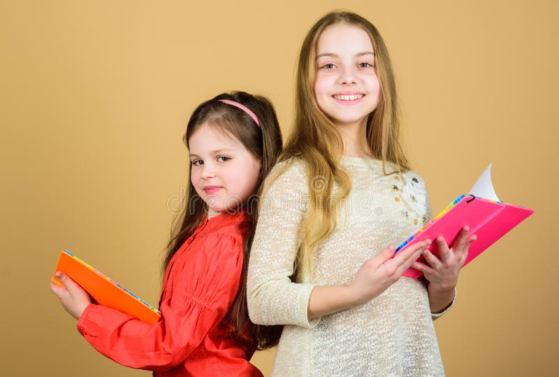 Opening doors through literacy. Kids girls with books or notepads. Education and kids literature. Favorite fairytale. Back to school. Sisters pick books to stock photos
