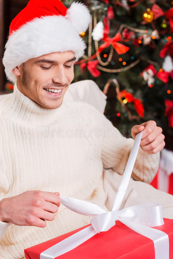 Opening his Christmas present. Top view of handsome young man in Santa hat opening gift box and smiling with Christmas Tree in the background stock images