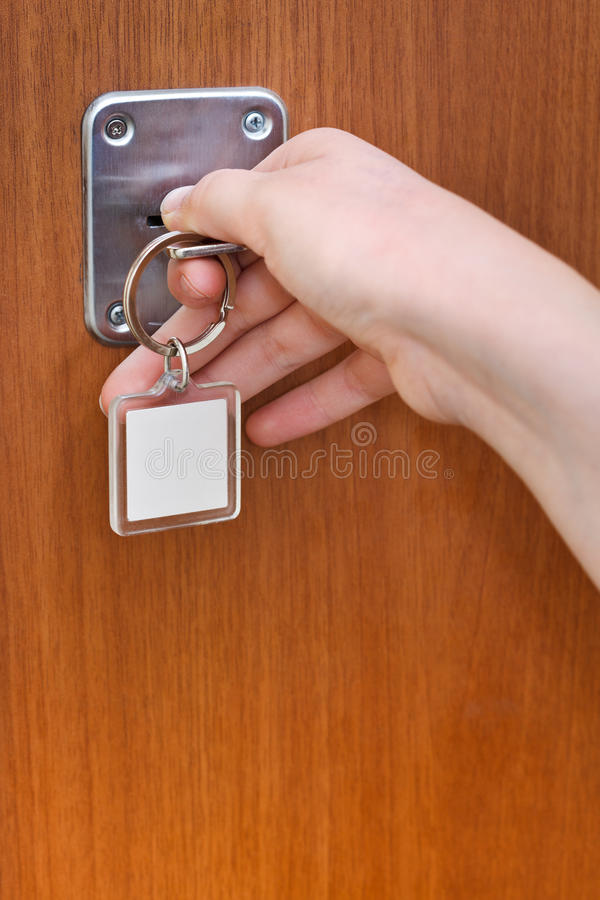Opening home door by key with blank keychain. Close up stock image