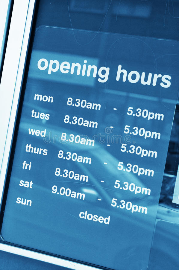Opening hours. Business opening hours in shop window royalty free stock photos