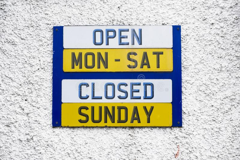 Opening hours shop sign Monday to Friday daytime closed Sunday. Uk royalty free stock image