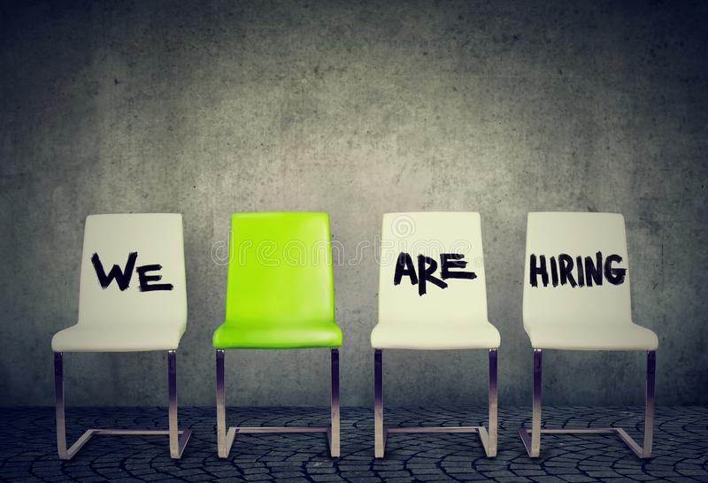 Opening for the job business concept. Row of white chairs and a green one royalty free stock photos