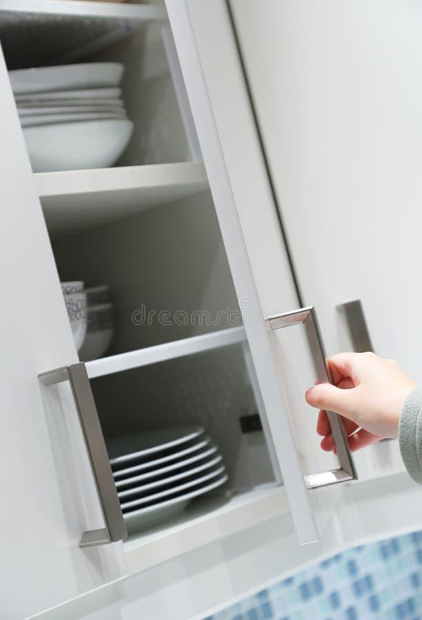 Opening kitchen cabinet door. Female opening (or closing) kitchen cabinet door stock photography