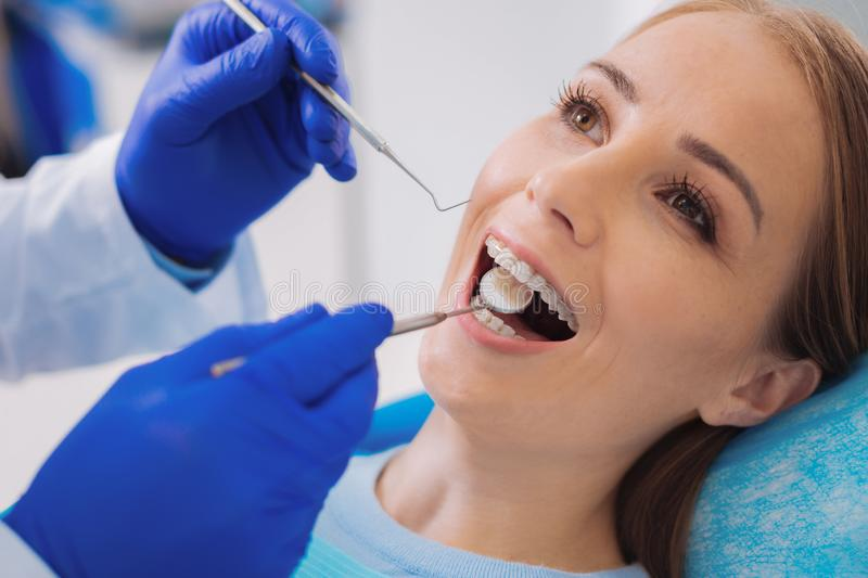 Positive patient opening her mouth while her dentist looking at the teeth. Opening mouth. Cheerful calm patient opening her mouth and a calm careful dentist stock images