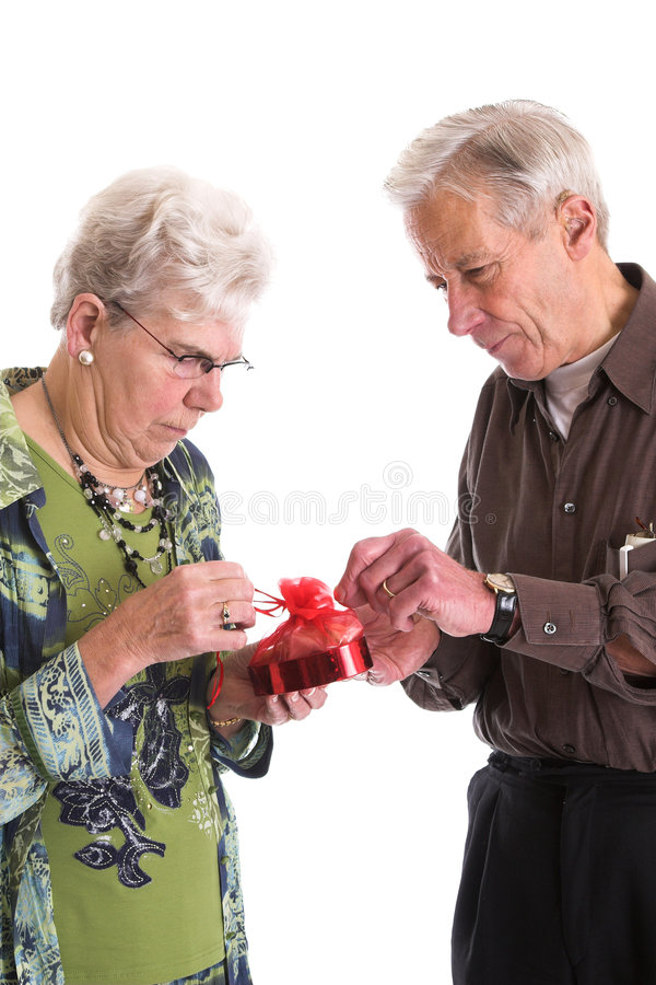 Opening the package. Loving senior couple opening a gift box of chocolates together stock photography