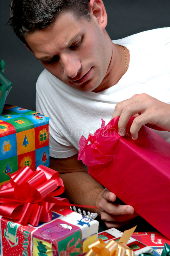 Opening Presents. A man opening a Christmas present stock images