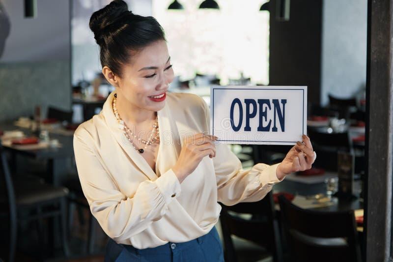 Opening restaurant. Happy elegant Vietnamese business lady hanging open signboard on restaurant door stock images