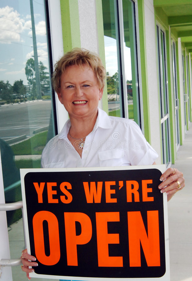 Opening retail shop. A senior woman holding a open sign in front of retail store royalty free stock photography