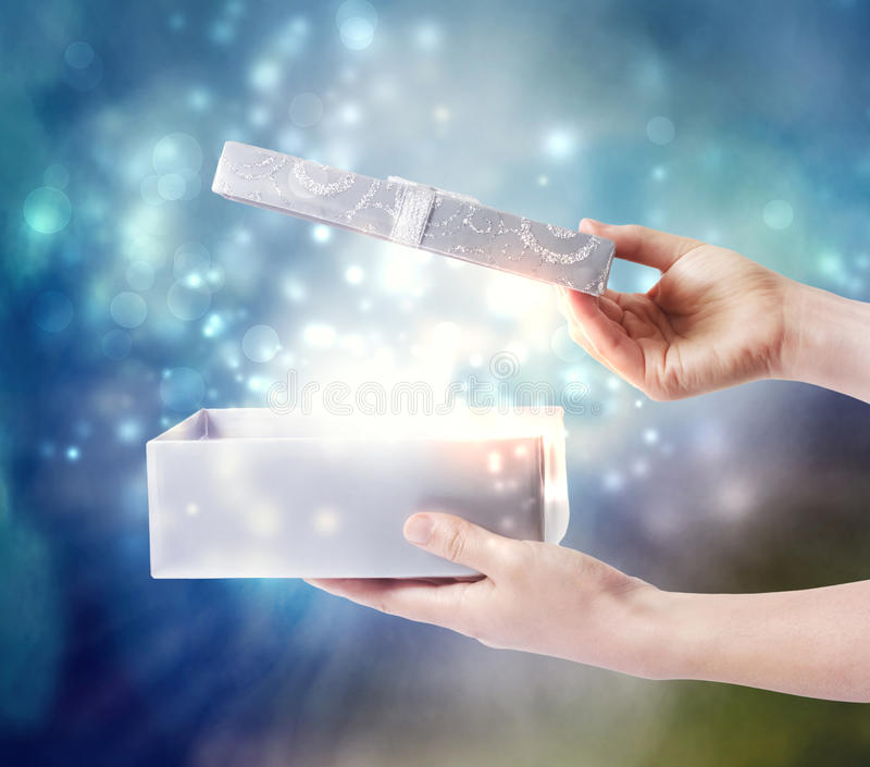 Opening a special present box. Opening a gift box with magical special effects lights royalty free stock image