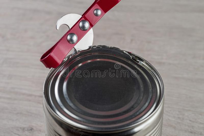 Opening a tin can with a can opener royalty free stock photos