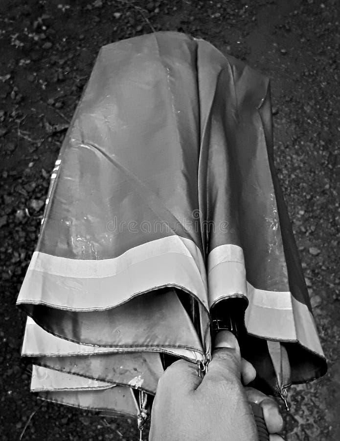 Opening umbrella. A farmer opening his old umbrella, black and white photo stock photos