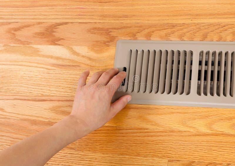 Opening up Floor Vent Heater. Horizontal photo of female hand opening up heater floor vent with Red Oak Floors in background stock photo