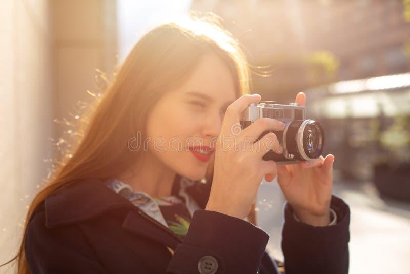Openlucht de herfst het glimlachen levensstijlportret van vrij jonge vrouw, die pret in de stad met camera, reisfoto hebben van royalty-vrije stock afbeelding
