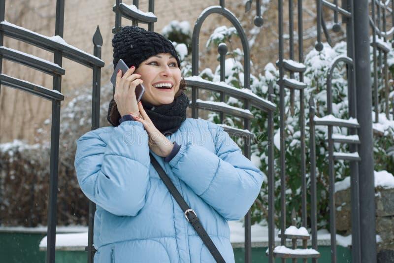 Openlucht de winterportret van rijpe vrouw met mobiele telefoon op sneeuwstadsstraat stock fotografie