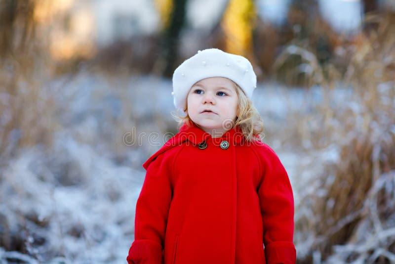 Openlucht de winterportret van weinig leuk peutermeisje in rode laag en witte manierhoed barret Gezond gelukkig babykind stock foto