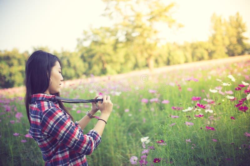 Openlucht de zomer het glimlachen levensstijlportret van vrij jonge vrouw die pret op het gebied van de kosmosbloem met de foto v royalty-vrije stock afbeelding