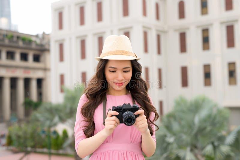 Openlucht de zomer het glimlachen levensstijlportret van vrij jonge vrouw die pret in de stad in Aziaat met de foto van de camera stock afbeelding