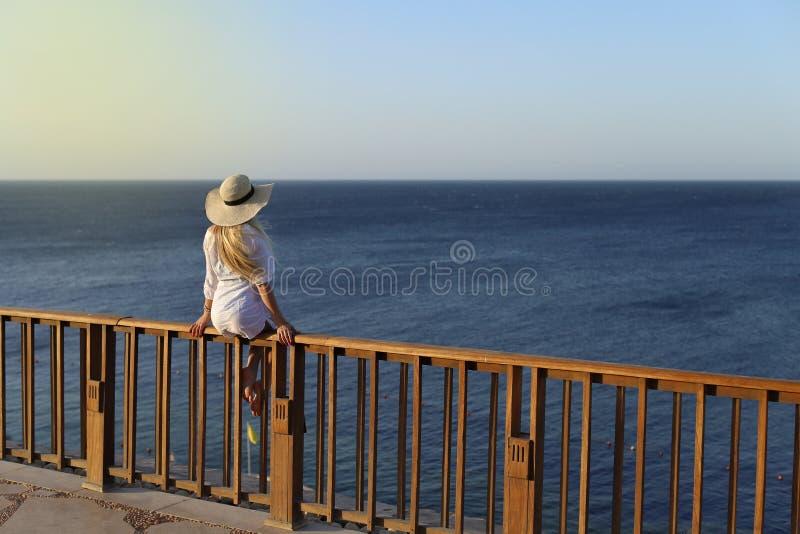 Openlucht de zomerportret van het jonge mooie vrouw kijken aan het overzees stock afbeelding