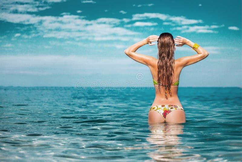 Openlucht de zomerportret van jonge mooie vrouw in bikini dichtbij het overzees bij tropisch strand stock afbeeldingen