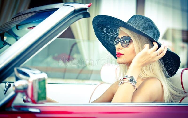 Openlucht de zomerportret van modieus blonde uitstekende vrouw die een convertibele rode retro auto drijven Modieus aantrekkelijk stock afbeeldingen