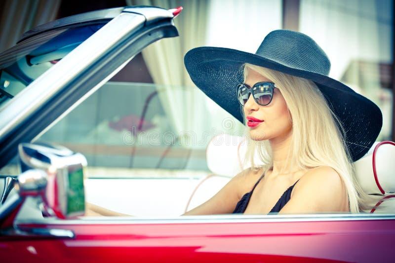 Openlucht de zomerportret van modieus blonde uitstekende vrouw die een convertibele rode retro auto drijven Modieus aantrekkelijk stock afbeelding