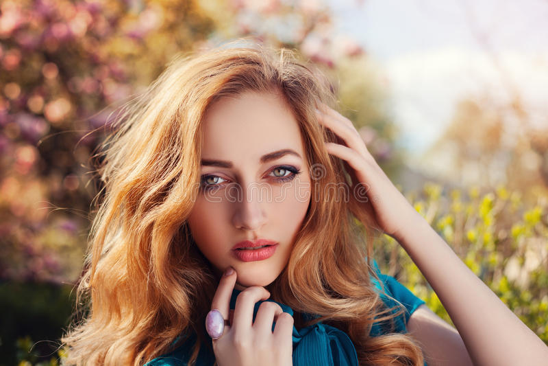 Openlucht dicht omhooggaand portret van het jonge mooie dame stellen dichtbij bloeiende boom ModelLooking bij Camera Meisje het d royalty-vrije stock afbeelding