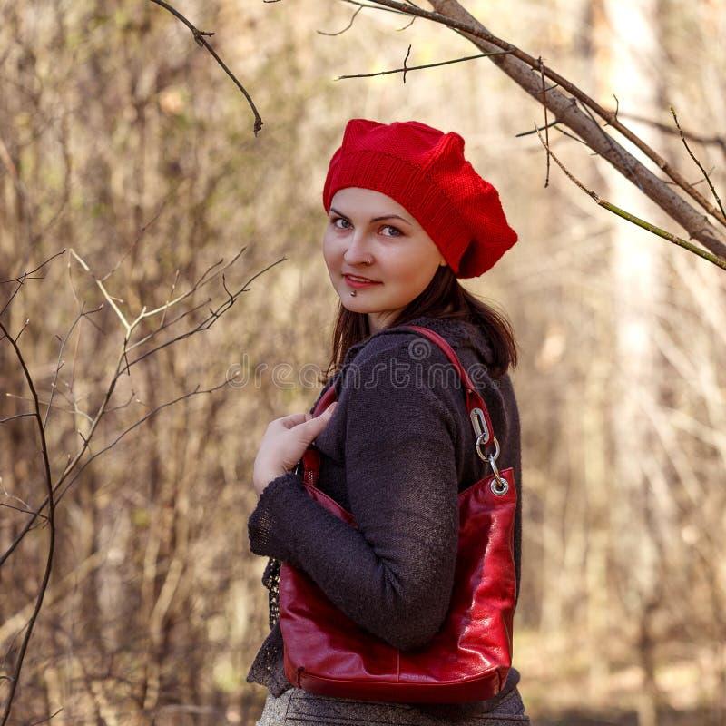Openlucht dicht omhooggaand portret van jong mooi gelukkig glimlachend meisje die Franse stijl rode gebreide baret dragen royalty-vrije stock fotografie
