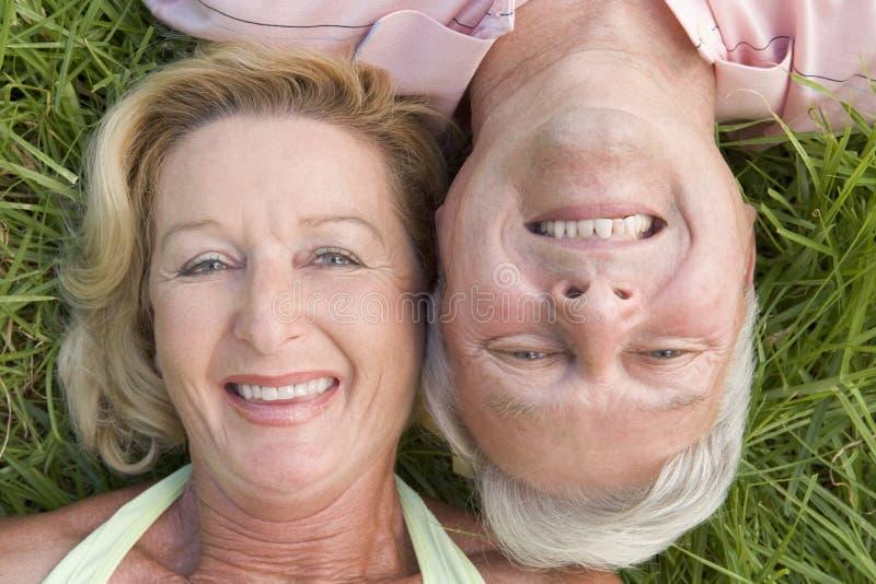 In openlucht en paar dat ontspant glimlacht royalty-vrije stock fotografie
