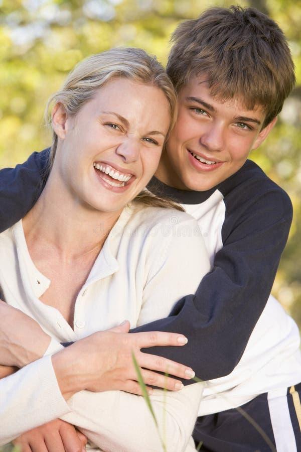 In openlucht en vrouw en jonge jongen die omhelzen glimlachen royalty-vrije stock afbeeldingen
