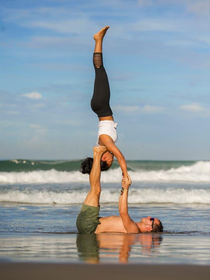 In openlucht in evenwicht brengt het jonge aantrekkelijke en geconcentreerde paar van het levensstijlportret van yogaacrobaten di royalty-vrije stock foto