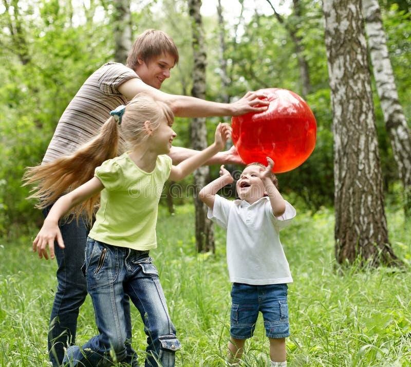Openlucht gelukkige familie plaing bal. stock fotografie