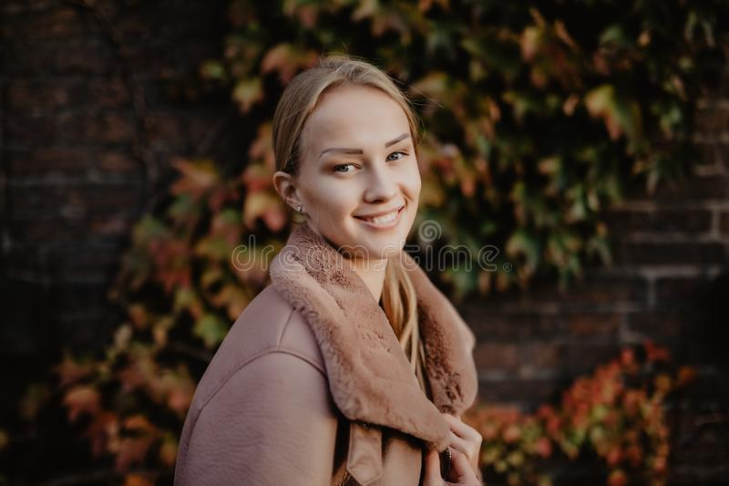 In openlucht het jonge de vrouw van het manierblonde stellen op de magische de herfstbladeren bij de dichtbijgelegen bouw als ach royalty-vrije stock foto's